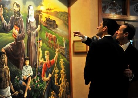 7. Benedictine College President Stephen D. Minnis shows U.S. Rep. Paul Ryan the floor-to-ceiling mural by Anthony Gude that depicts the influence of the Benedictines in Atchison, Kan.