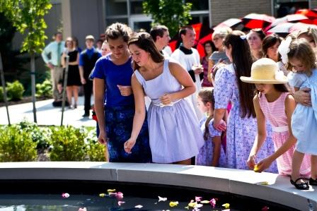 Students, faculty, staff and participants with Marian names dropped rose petals into the basin of the Our Lady of Grace fountain at its dedication.